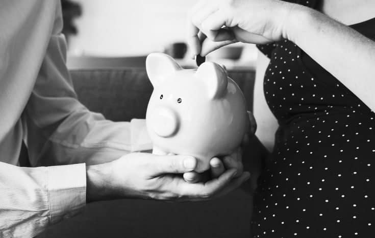 Man and woman saving money in piggy bank #nospendchallenge