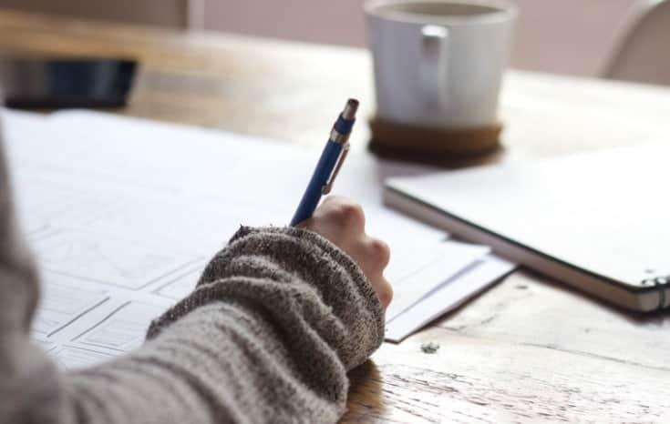 women writing her no spend challenge plan