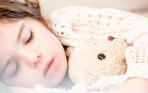 child sleeping with teddy bear, featured image for how to create a bedtime routine for kids that actually works
