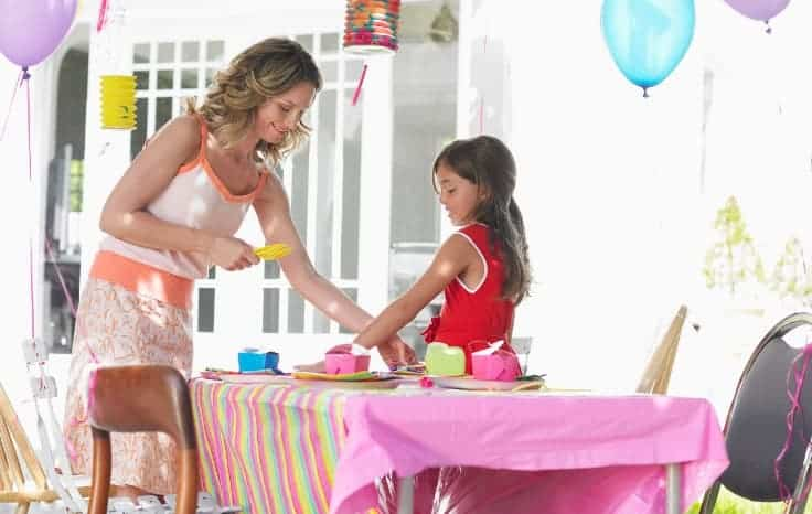 Mom and daughter setting up summer birthday party